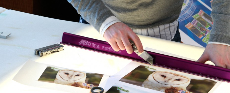 Cutting posters on lit table